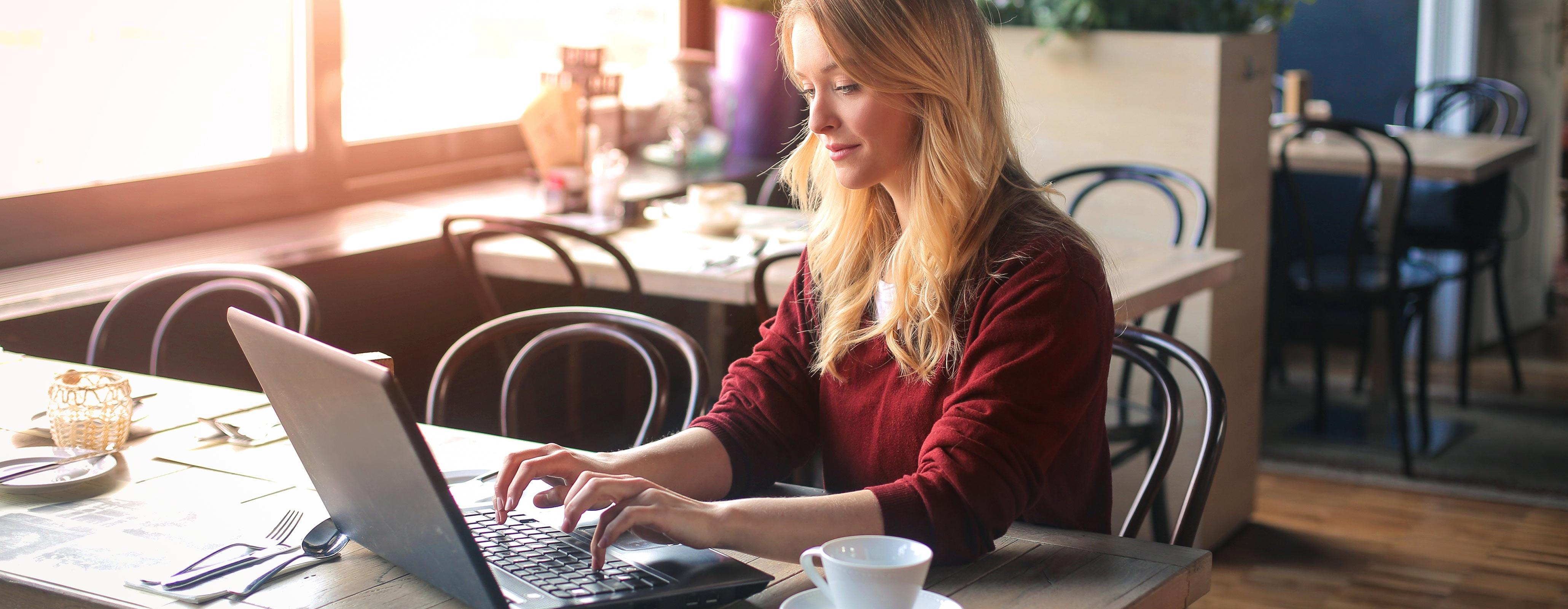 Vrouw in koffietent met laptop