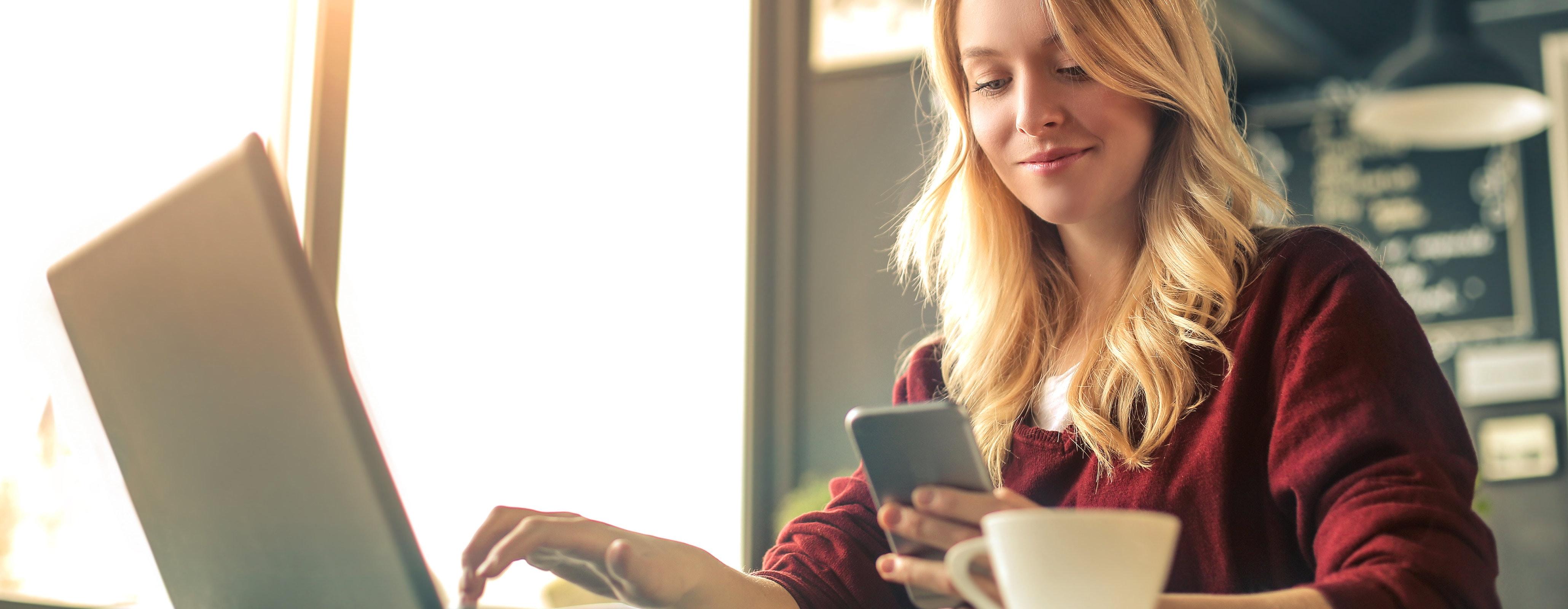 Vrouw achter laptop met mobiel