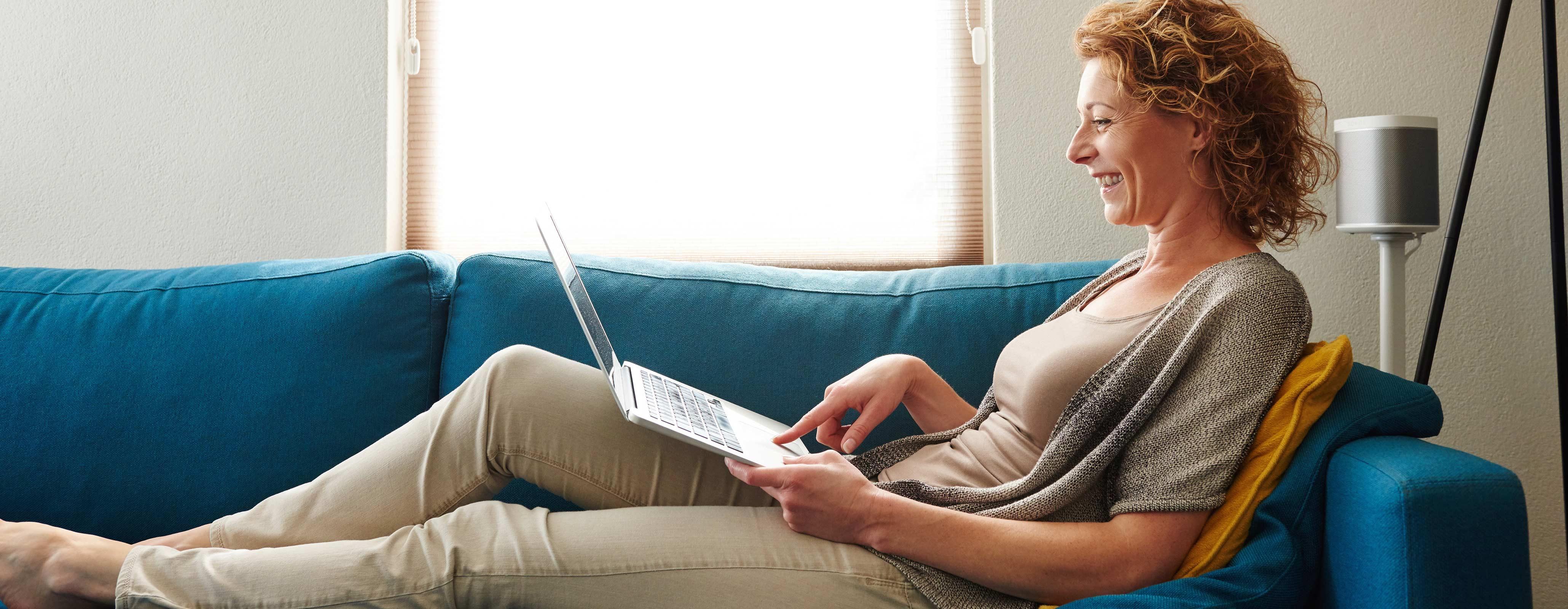 Vrouw op bank kijkt naar laptop