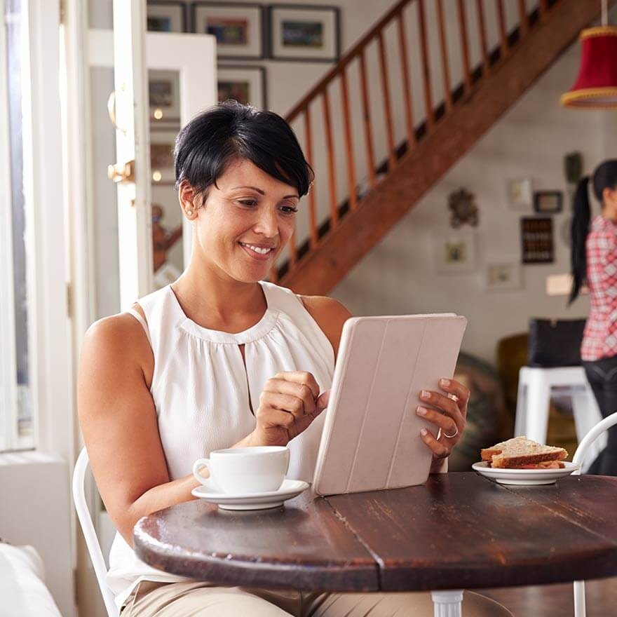 Vrouw in een koffietentje met haar tablet