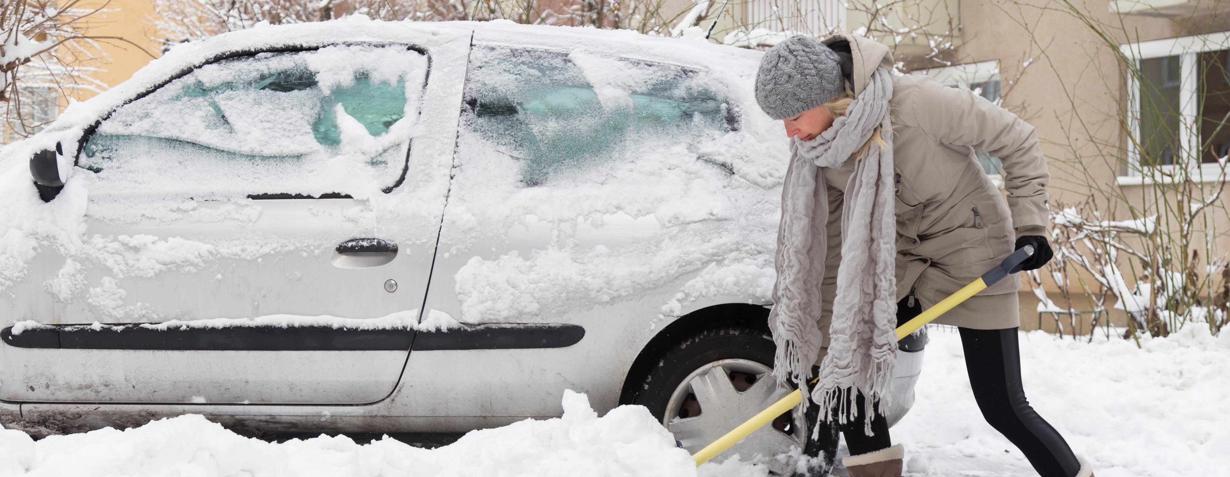 Vrouw schept sneeuw weg bij auto
