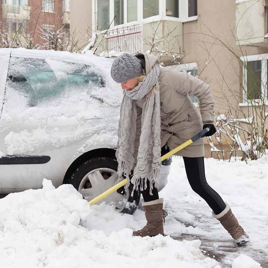 Vrouw schept sneeuw bij auto weg