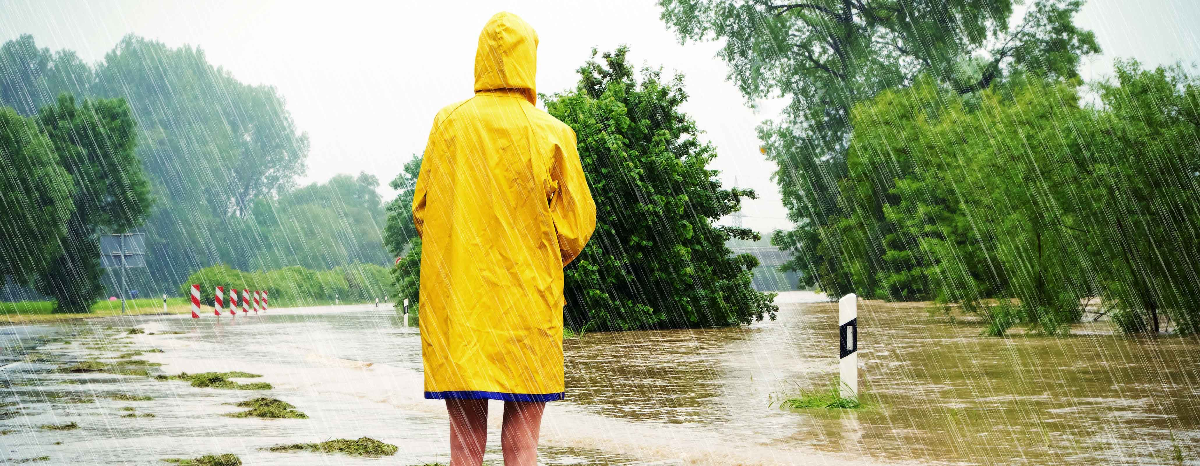 Persoon staat in hevige regen