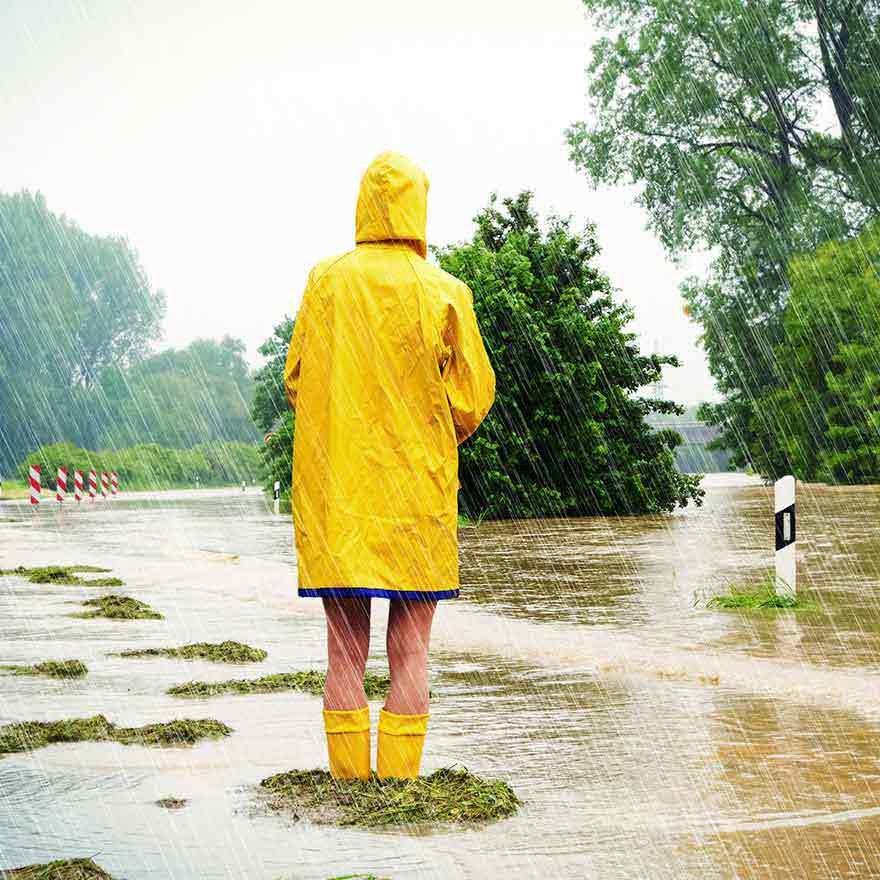 Kind met regenlaarzen en regenpak aan staat in noodweer