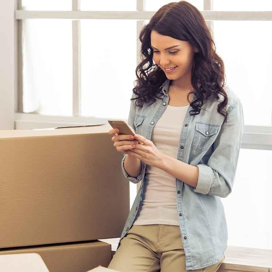 Vrouw tussen verhuisdozen kijkt op mobiel
