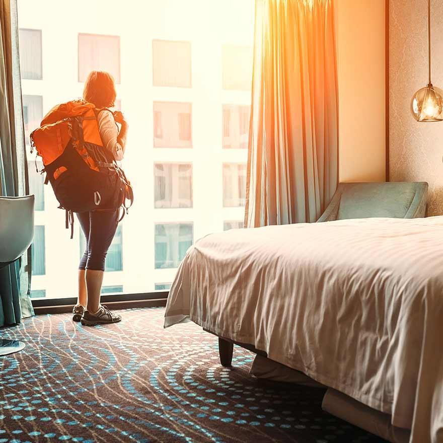 Vrouw met rugzak in hotelkamer
