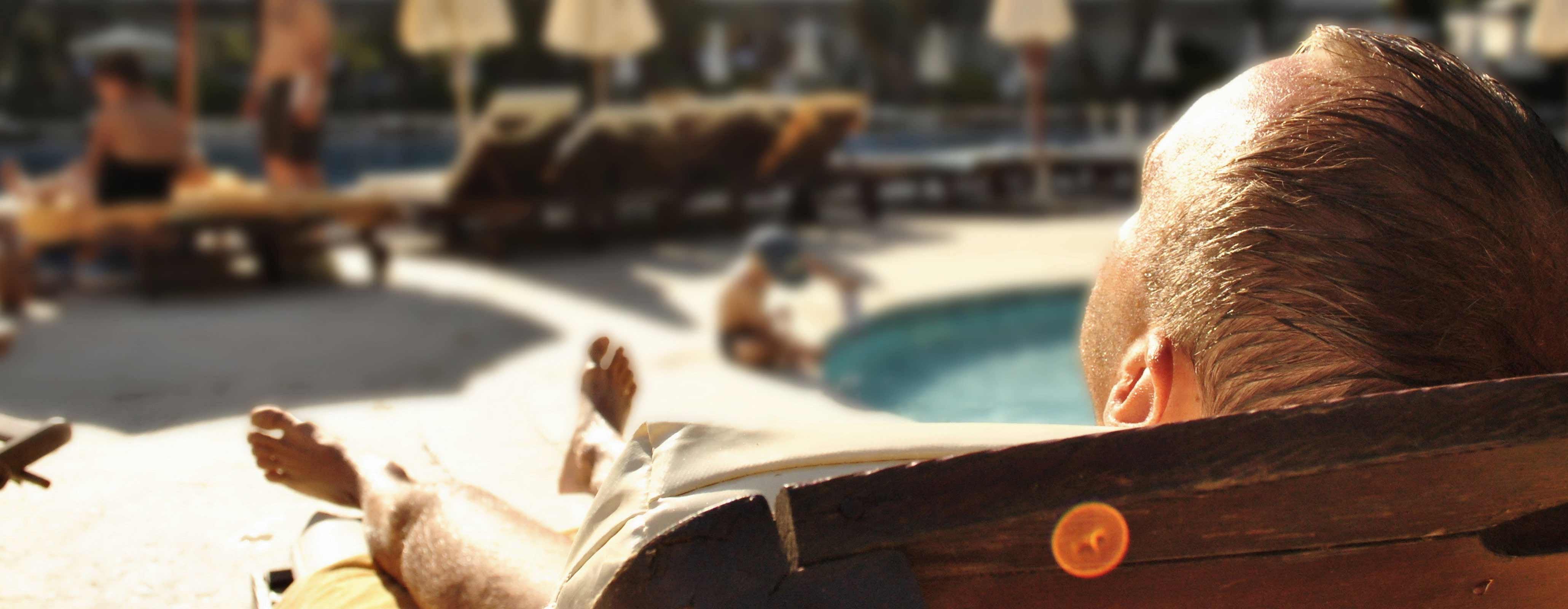 Man ligt onbezorgd aan zwembad tijdens vakantie