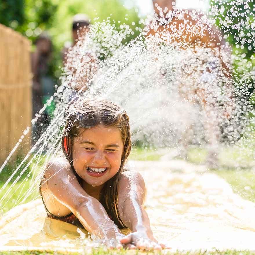Meisje in de tuin met water aan het spelen