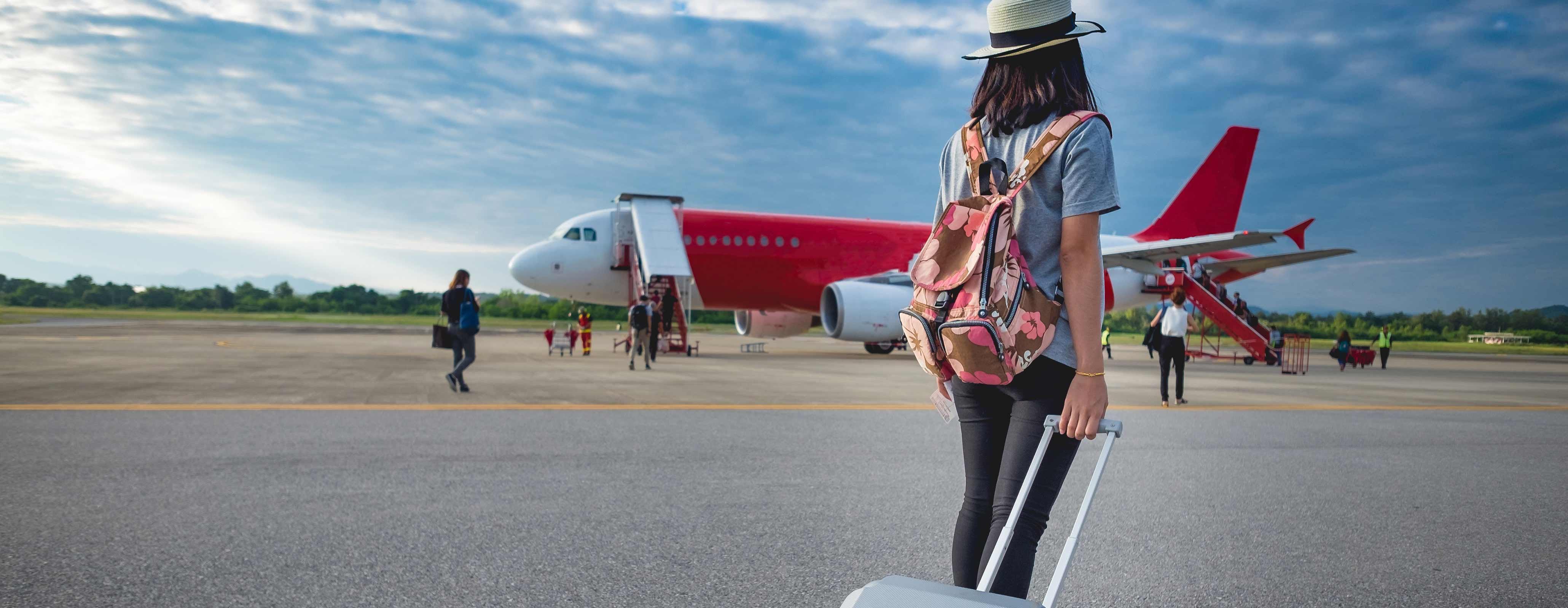 Vrouw met koffer bij het vliegtuig