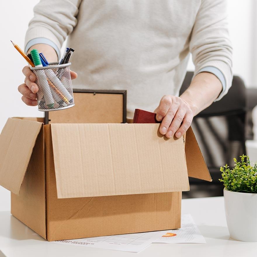 persoon pakt spullen in doos
