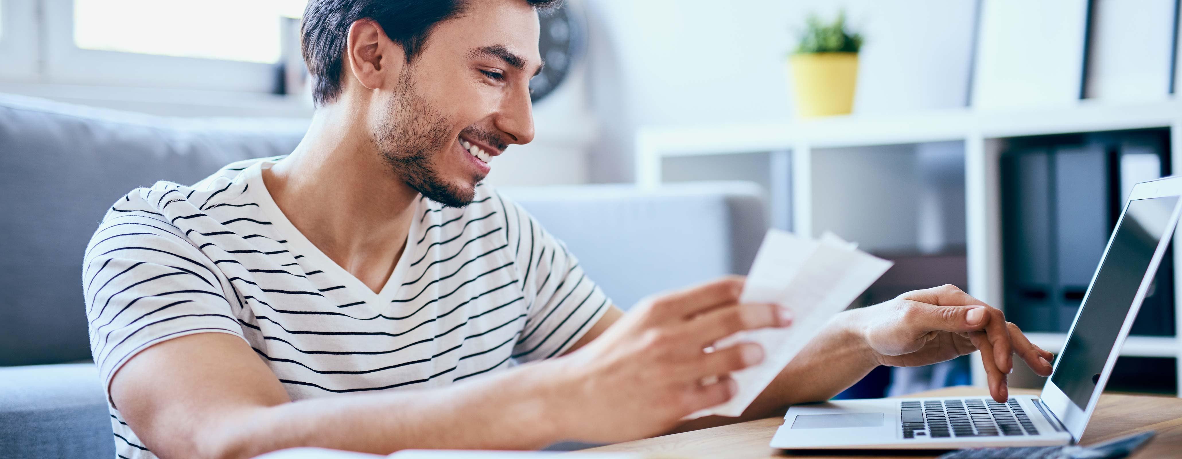 Man met laptop en papieren