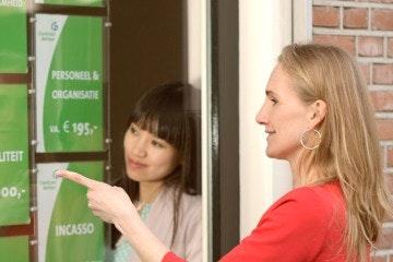 Vrouw zoekt een dienst uit in de etalage - wat kunt u van de ondernemerswinkel verwachten