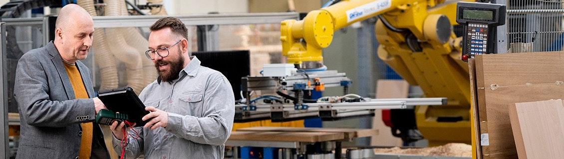 Twee mannen lopen inspectierapport door van de fabriek | Gele robotarm op de achtergrond | Ondernemerswinkel | Continuïteit in uw bedrijf